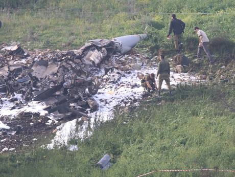 Israeli security forces walk next to the remains of an F-16 Israeli war plane near the Israeli villa