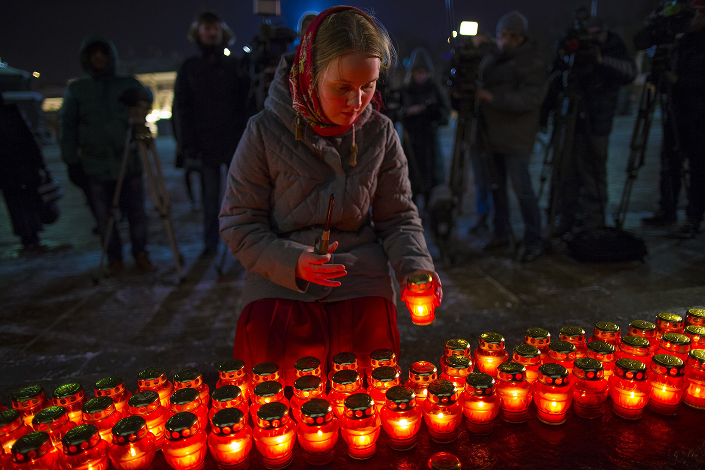 A girl places a candle as a group gather at the Cathedral of Christ the Savior in Moscow to light 71
