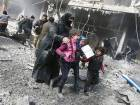A Syrian woman and children run for cover amid the rubble of buildings following government bombing in Hammuriyeh town on Sunday.