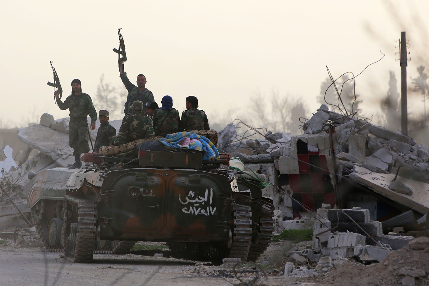 Syrian government forces brandish their weapons while standing on an armoured personnel carrier afte