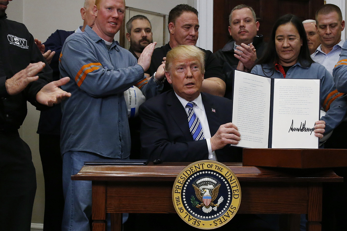 U.S. President Donald Trump holds up a proclamation during a White House ceremony to establish tarif