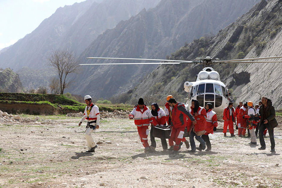 Rescuers carry the body of a passenger of a Turkish private jet that crashed in the Zagros Mountains