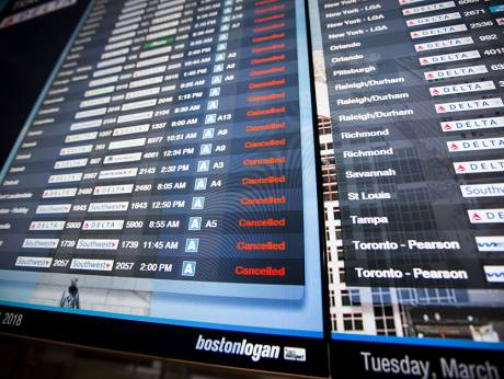 Information boards at Logan International Airport show hundreds of cancelled flights