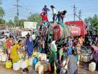 People gather around a municipal corporation water tanker to get their supply of water, in Bhopal.