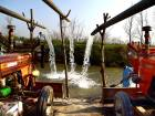 Pakistani farmers use tractors to pump water used to irrigate fields at the Kabul River on the outskirts of Peshawar.