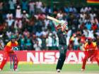 Rameez Shahzad of the UAE hits a six as Zimbabwe's Brendan Taylor hovers over the stumps in Harare.