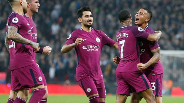 Manchester City's Raheem Sterling celebrates with team mates after scoring his sides third goal