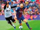 Valencia's Carlos Soler (left) vies with Barcelona's Andres Iniesta. Iniesta has signed a 'lifetime contract' with Barcelona.