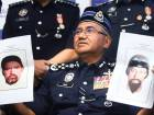 Inspector General of Royal Malaysian Police Mohammad Fuzi Harun shows two picture of suspects in the killing of a Palestinian man during a press conference in Kuala Lumpur.