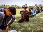 Students took an exam in a field as their school was too damaged by fighting between Taliban and government forces in Archi