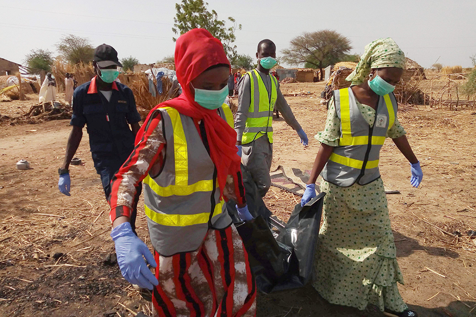 Officials of Borno State Emergency Management Agency carry the body of a victim