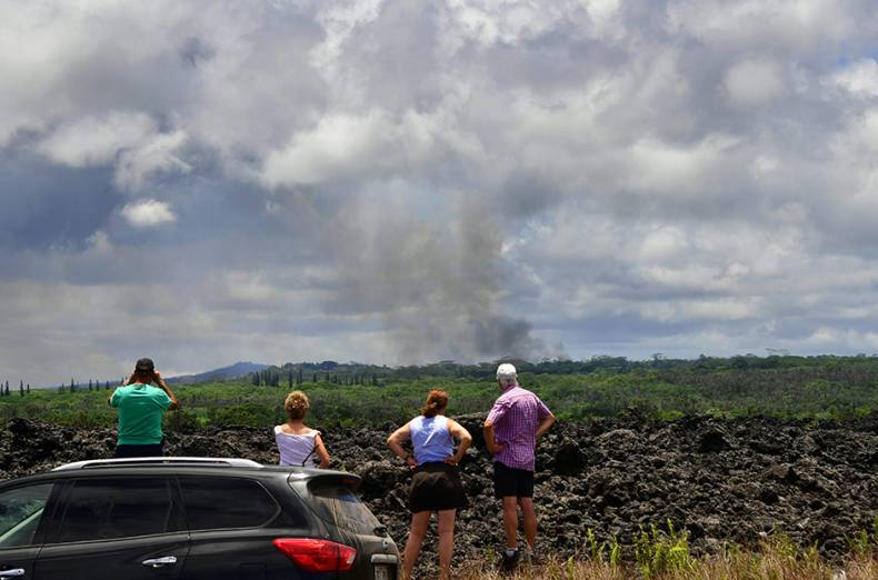 people-stop-their-vehicle-on-the-side-of-the-road-for-a-view-of-a-plume-of-smoke-rising