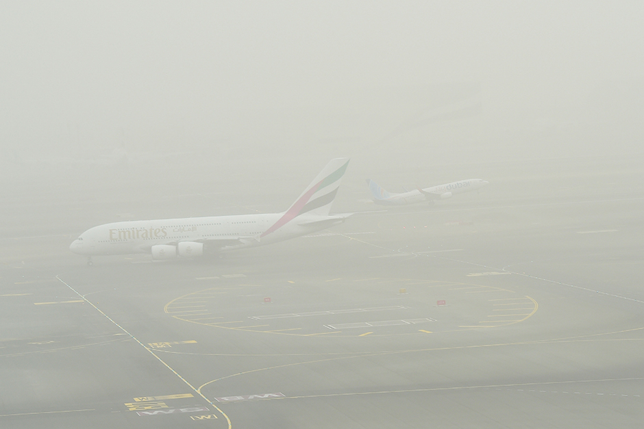 An Emirates plane is seen taxiing during the sandstorm at Dubai Airport