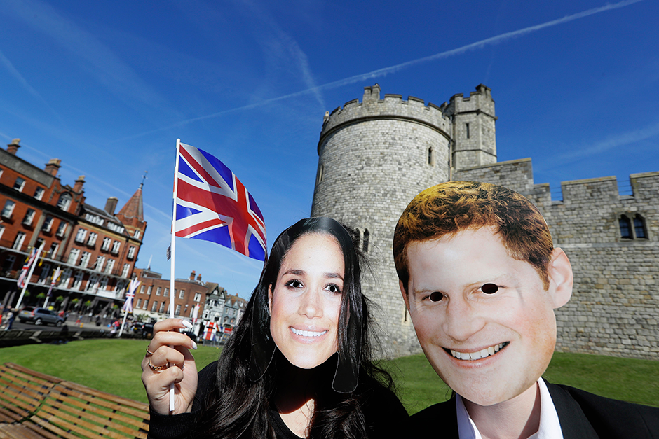 People wearing face masks of Britain's Prince Harry and Meghan Markle