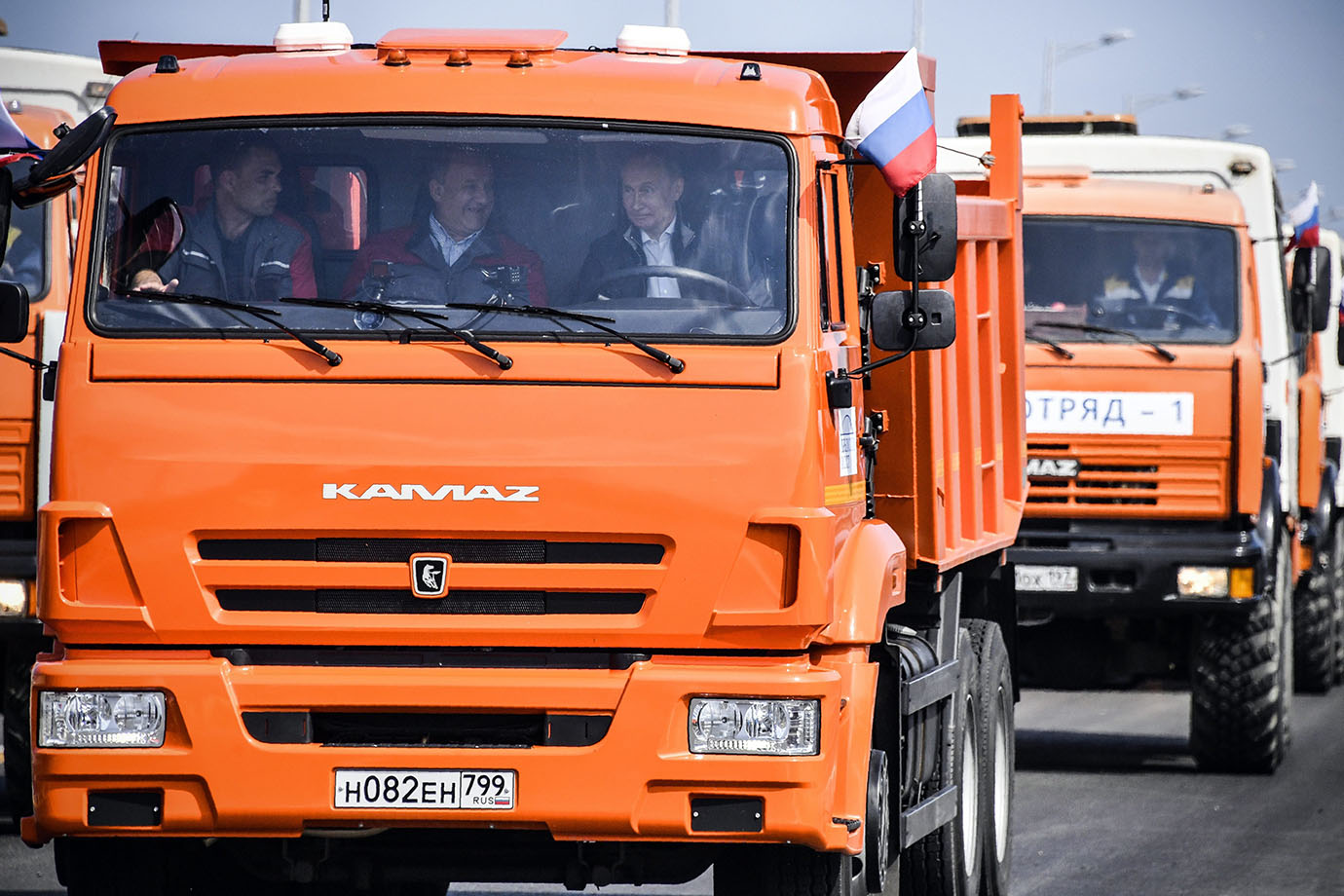 Russian President Vladimir Putin, centre right, drives a truck to officially open the much-anticipat