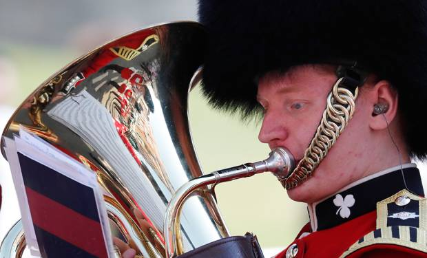 A military brass band player plays a tuba