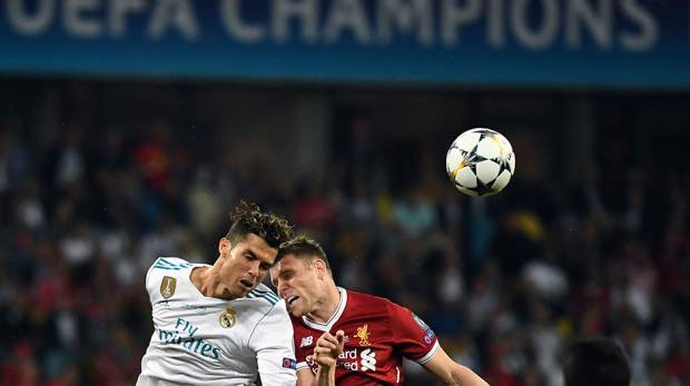 Real Madrid's Cristiano Ronaldo and Liverpool's James Milner jump for the ball