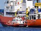 """An Italian Coast Guard boat approaches the French NGO """"SOS Mediterranee"""" Aquarius ship as migrants are being transferred, in the Mediterranean Sea, Tuesday, June 12, 2018."""