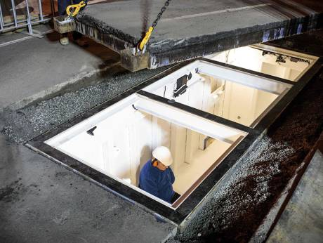 Mike Parr, 73, sitting in a coffin-like steel box as he is entombed under a busy road in Hobart