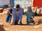 Eight year-old Maya Mohammad Ali Merhi, using prosthetic legs made by her father from tincans, walks with him and another child in a camp for displaced people in Idlib.