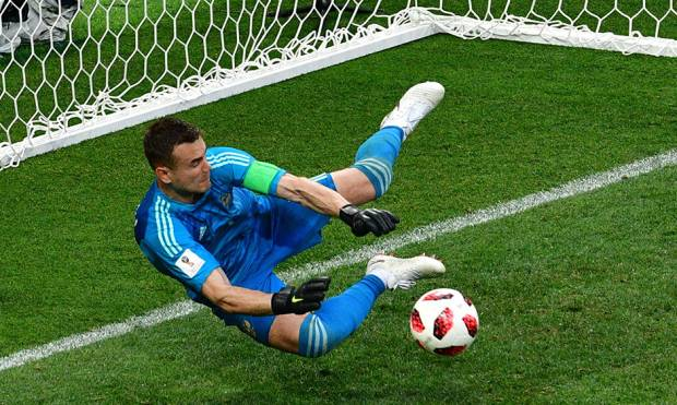 Russia's goalkeeper Igor Akinfeev saves the ball kicked by Spain's midfielder Koke