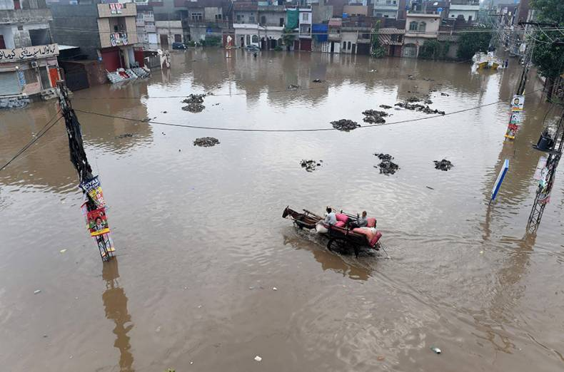 a-man-rides-on-his-horse-cart-through-a-flooded-square-after-heavy-rains-in-lahore