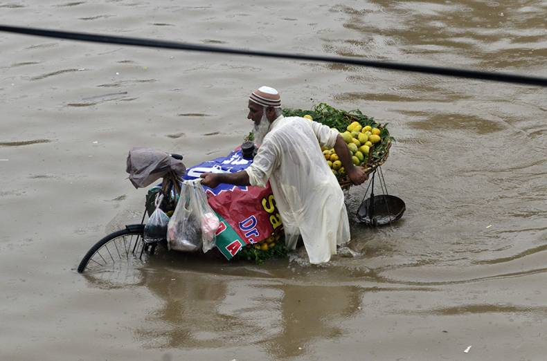a-vendor-pushes-a-bike-loaded-with-mangoes-along-a-flooded-street-after-heavy-rains-in-lahore