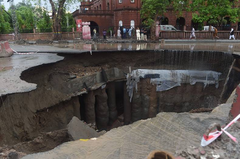 residents-gather-around-a-road-cave-in-caused-by-heavy-rains-in-lahore