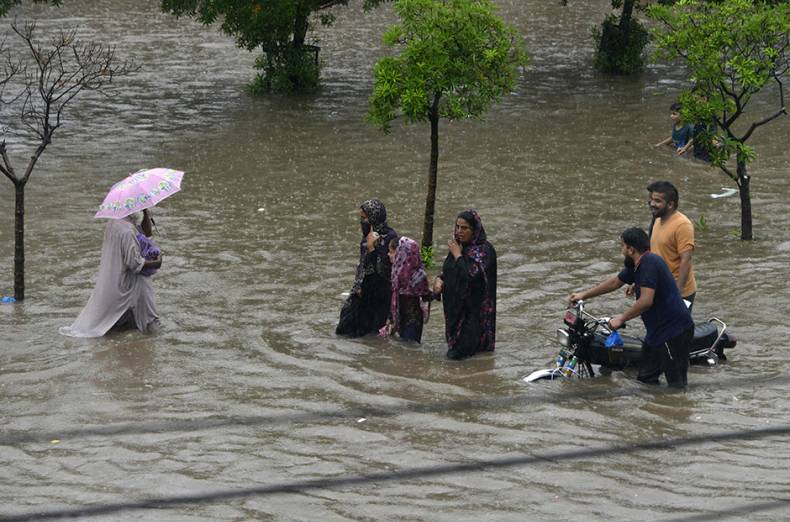 residents-wade-through-a-flooded-street-during-heavy-rain-in-lahore