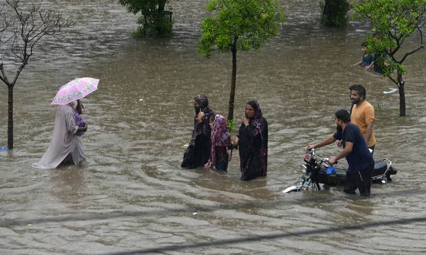Residents wade through a flooded street during heavy rain in Lahore