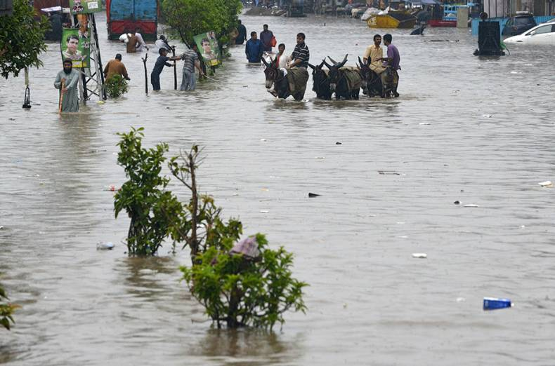 labourers-ride-on-donkeys-along-a-flooded-street-after-heavy-rains-in-lahore