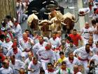 Revellers run in front of Puerto de San Lorenzo's fighting bulls during the running of the bulls at the San Fermin Festival, in Pamplona, northern Spain.