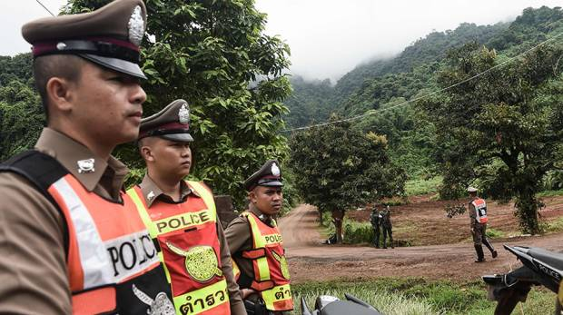 Thai police stand guard at Tham Luang cave area as operations continue for the 12 boys and their coa