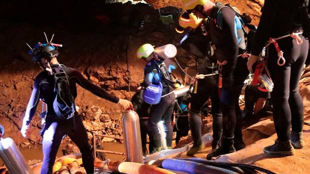 Thai rescue team members walk inside a cave where 12 boys and their football coach have been trapped