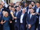 France's goalkeeper Hugo Lloris (C) holds the trophy next to France's coach Didier Deschamps (C, right) as French President Emmanuel Macron (C, left) and his wife Brigitte Macron (2ndL) welcome players and staff members of the French national football team after they won the Russia 2018 World Cup final football match during a reception at the Elysee Presidential Palace on July 16, 2018 in Paris.  France celebrated their second World Cup win 20 years after their maiden triumph on July 15, 2018, overcoming a passionate Croatia side 4-2 in one of the most gripping finals in recent history. / AFP / LUDOVIC MARIN
