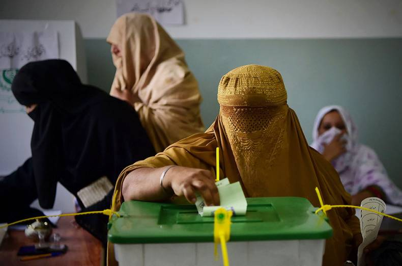 a-burqa-clad-woman-casts-her-vote-during-pakistan-s-general-election-at-a-polling-station