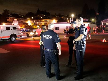 Law enforcement officials stand at a staging area, at the ferry terminal in Washington, near a plane