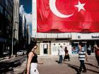 Pedestrians pass a giant Turkish national flag hanging above a DenizBank bank branch in Istanbul. Emirates NBD agreed to buy the Turkish bank from Russia's Sberbank in May.