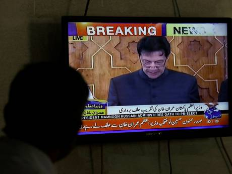 A man looks at a television screen showing Imran Khan being sworn in as Prime Minister