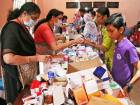 Flood-affected people receive free medicines inside a college, which has been converted into a temporary relief camp, in Aluva in Kerala.