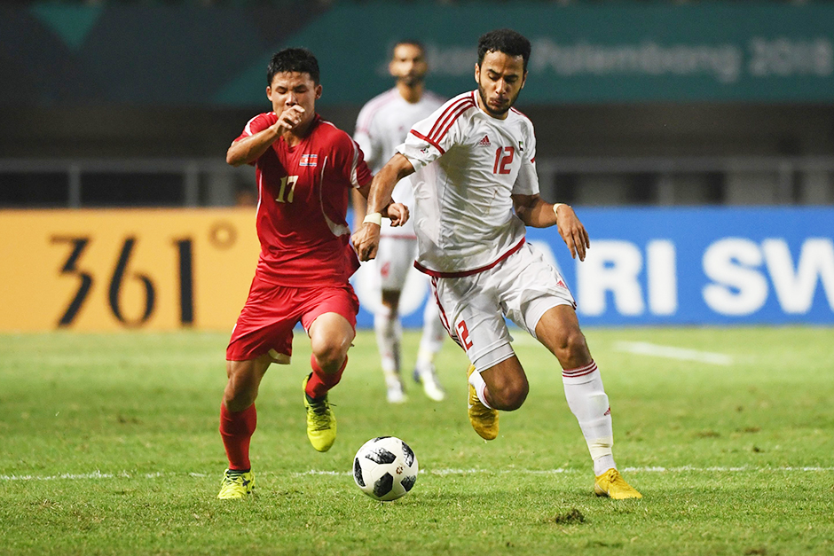 UAE's Khaled Aldhanhani (R) and North Korea's Kang Kuk Chol (L) fight for the ball
