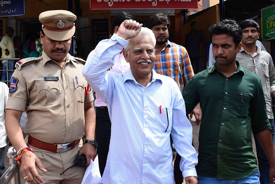 Activist Varara Rao is escorted by policemen as he is arrested in Hyderabad