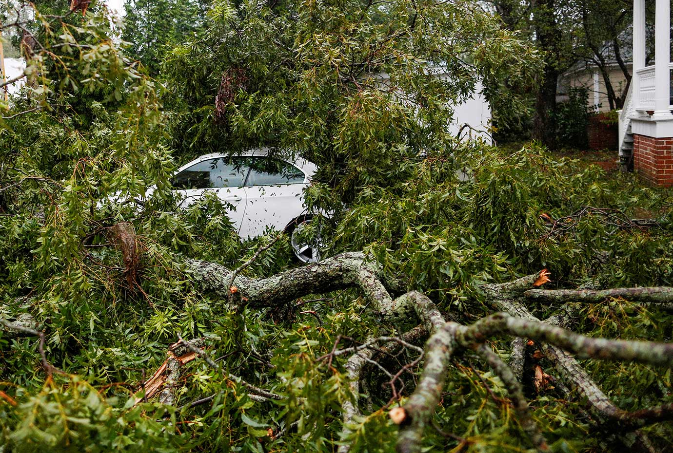 Felled trees and other debris cover a car during the passing of Hurricane Florence in the town of Ne