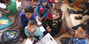 War-displaced Syrian kids study on the ground
