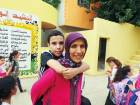 Mum carries son on her back to school