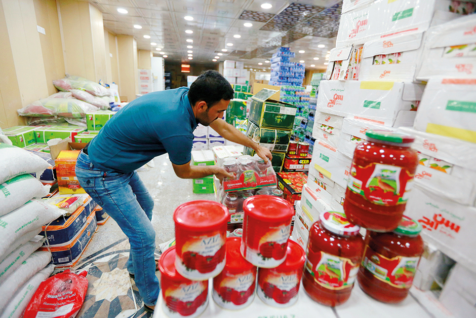 A shop worker arranges the cans of Iranian tomato paste at a super market in the city of Najaf