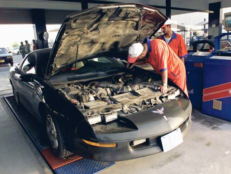 A workshop mechanic conducts a pre-registration check on a car at a 'Tasjeel' centre