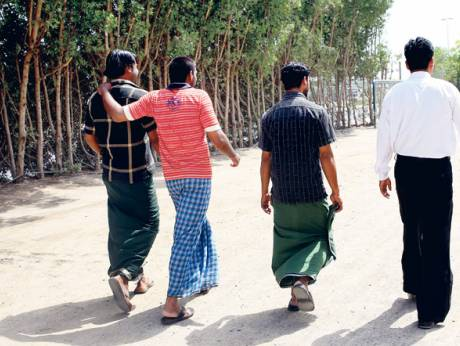 Men wearing lungis strolling in a Sharjah locality