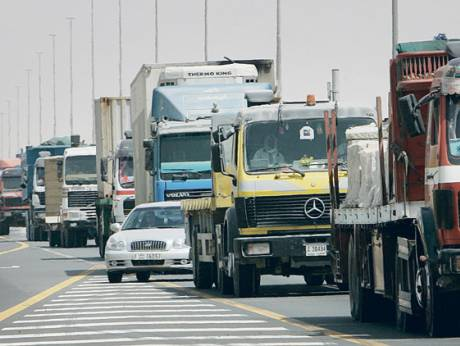 A car moves in between trucks and heavy vehicles on Emirates Road in Dubai