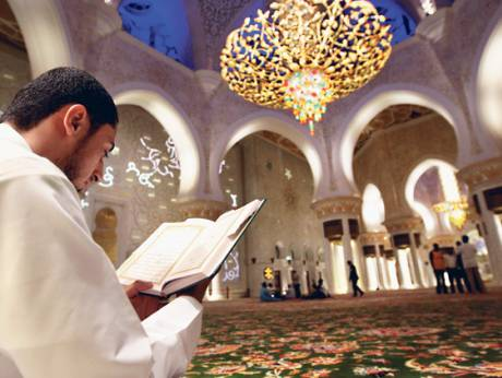 A man reads the Quran at the Shaikh Zayed Mosque